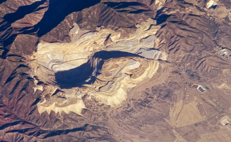 The Bingham Canyon Mine (image center) is one of the largest open-pit mines in the world, measuring over 4 kilometers wide and 1,200 meters deep. Located about 30 kilometers southwest of Salt Lake City, Utah, the mine exploits a porphyry copper deposit, a geological structure formed by crystal-rich magma moving upwards through pre-existing rock layers. As the magma cools and crystallizes, it forms an igneous rock with large crystals embedded in a fine-grained matrix, known as a porphyry. Hot fluids circulate through the magma and surrounding rocks via fractures, depositing copper-bearing and other minerals in spatial patterns that a geologist recognizes as a potential porphyry copper deposit. NASA image
