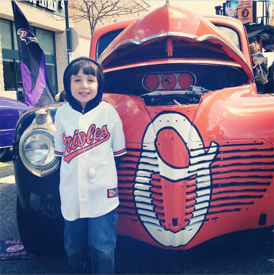 "Young boy in white Orioles shirt poses with classic car painted in Orioles orange and white ""O"" on grill"