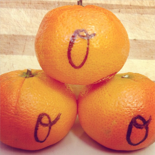Three oranges with Baltimore Orioles style Os drawn on them in black marker