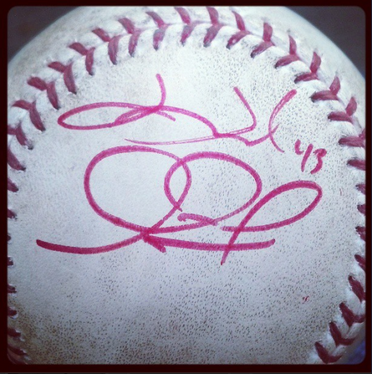Baseball signed in red marker by Orioles players Jim Johnson and Adam Jones
