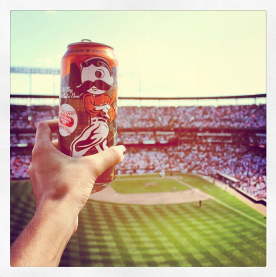 Orange Natty Boh beer can hoisted by a fan's hand from the right field upper deck at Camden Yards, with baseball field and other stands in background