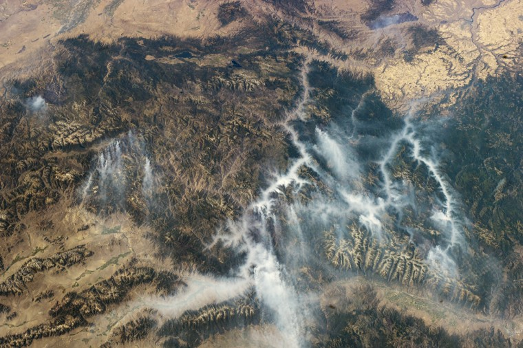 """Taken with a short lens (45 millimeters), this west-looking astronaut photograph has a field of view covering much of the forested region of central Idaho. The dark areas are wooded mountains - the Salmon River Mountains (image left), the Bitterroots (lower right) and Clearwater Mountains (right). All three areas experienced wildfires in September 2012. Smaller fire """"complexes"""" appear as tendrils of smoke near the sources - for example, the Halstead fires - and as major smoke plumes from fires in the densest forests - such as the Mustang fire complex. NASA image"""