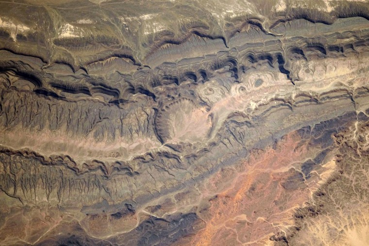 "The Ouarkziz Impact Crater is located in northwestern Algeria, close to the border with Morocco. The crater was formed by a meteor impact less than 70 million years ago, during the late Cretaceous Period of the Mesozoic Era, or ""Age of Dinosaurs."" Originally called Tindouf, the 3.5-kilometer wide crater (image center) has been heavily eroded since its formation; however, its circular morphology is highlighted by exposures of older sedimentary rock layers that form roughly northwest to southeast-trending ridgelines. From the vantage point of an astronaut on the International Space Station, the impact crater is clearly visible with a magnifying camera lens."