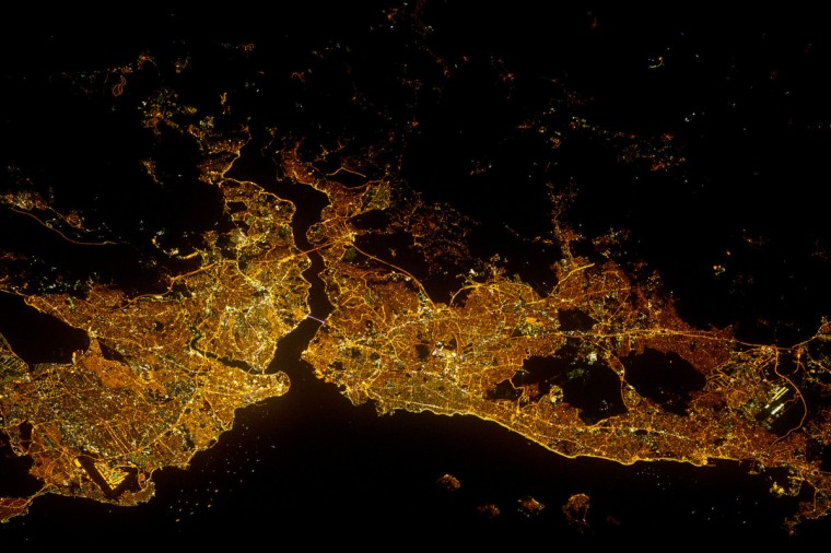 Most of Istanbul's Asian suburbs (image right) appear in this night view from the International Space Station, but only about half the area of the city on the European side is visible. The margins of the metropolitan area are clearly visible at night, more so than in daylight images in daylight images. The Bosporus strait (also spelled Bosphorus) famously separates the two halves of the city and links the small Sea of Marmara (and the Mediterranean Sea) to the Black Sea. The strait is 31 kilometers (19 miles) long, most of which is visible in this view. The Bosporus is a very busy waterway, with larger ships passing north-south between the Black Sea and the Mediterranean, while competing with numerous ferries that cross east-west between the two halves of the city. NASA image