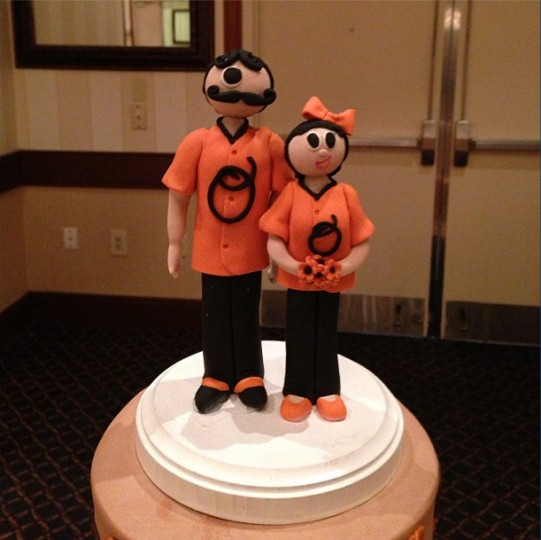 Bride and groom wedding cake toppers inspired by the Mr. Boh Natty Boh beer characer in orange and black Orioles gear