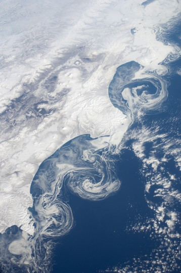 The vantage point from orbit on the International Space Station (ISS) frequently affords astronauts with the opportunity to observe processes that are impossible to see on the ground. The winter season blankets the Kamchatka Peninsula of Russia in snow, but significant amounts of sea ice can also form and collect along the Pacific coastline. As ice floes grind against each other, they produce smaller floes that can be moved by wind and currents. The irregular southeastern coastline of Kamchatka provokes large, circular eddy currents to spin off from the main southwestward-flowing Kamchatka current. Three such eddies are highlighted by surface ice floe patterns at image center. The patterns are very difficult (and dangerous) to navigate in an ocean vessel. NASA image