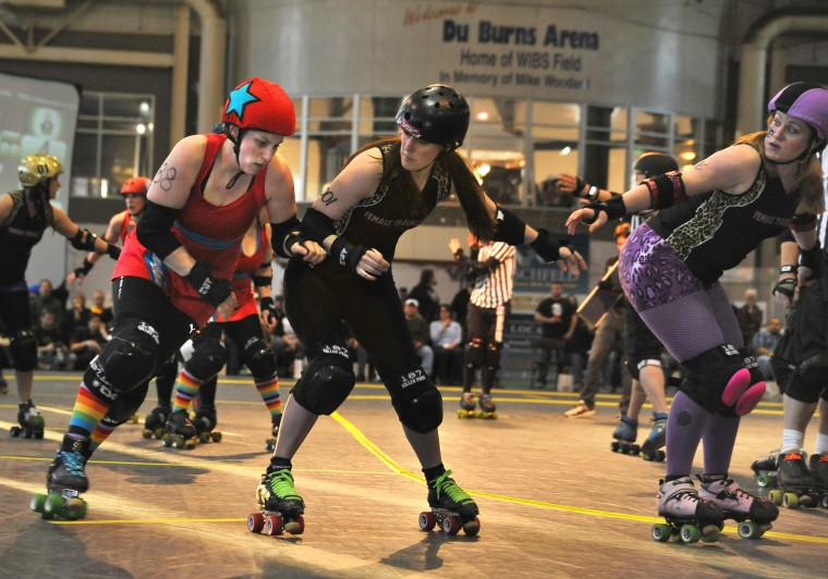 Philly's Independence Dolls jammer, Kong, left, moves to the outside to get past Charm City's Female Trouble blocker Jeanne Dark, center, and pivot, Smearin' Off Ice, right, in the first game of the night. (Amy Davis / Baltimore Sun)