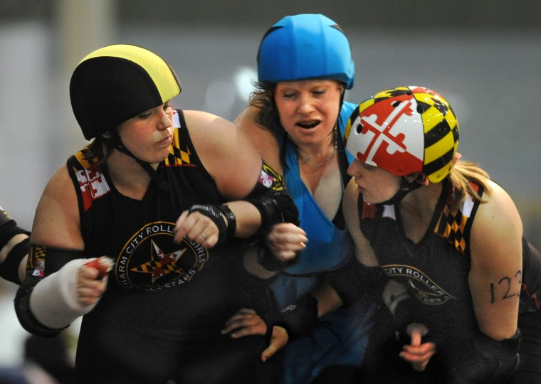 Philly's LIberty Belles jammer Teflon Donna, center, tries to get past All Stars blockers Battery Operated, left, and Mary Busch, right. (Amy Davis / Baltimore Sun)