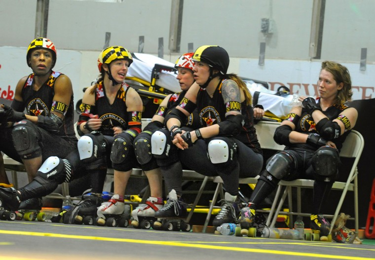 I.M. Pain, icing her bruised shoulder, right, is briefly on the bench with All Stars teammates, from left, Uvetta Work, Holly Gohardly, Lady Quebeaum, and Colleen Best. (Amy Davis / Baltimore Sun)