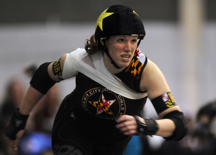 With her bruised shoulder bandaged, I.M. Pain, co-captain of the Charm City Roller Girls All Stars team, returns to the action, taking her turn as the jammer. (Amy Davis / Baltimore Sun)