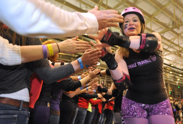 Fans ring the track to high-five all the players, including Female Trouble's Smearin' Off Ice, right, at the end of their match against Philly's Independence Dolls. (Amy Davis / Baltimore Sun)