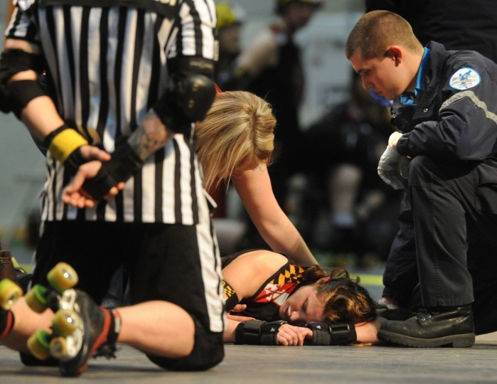 Baltmore's All Stars bench coach Blind Banshee leans over I.M. Pain (Kacey Huntington), who was knocked down by a direct hit to her shoulder midway through the first period. (Amy Davis / Baltimore Sun)