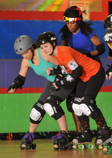 Beta Blockher, left, and Sadie Stingray, center, practice blocking Nuckin' Futz, behind them in the role of jammer, at a Bootcamp training session for the Charm City Roller Girls held at Skateland North Point. (Amy Davis / Baltimore Sun)
