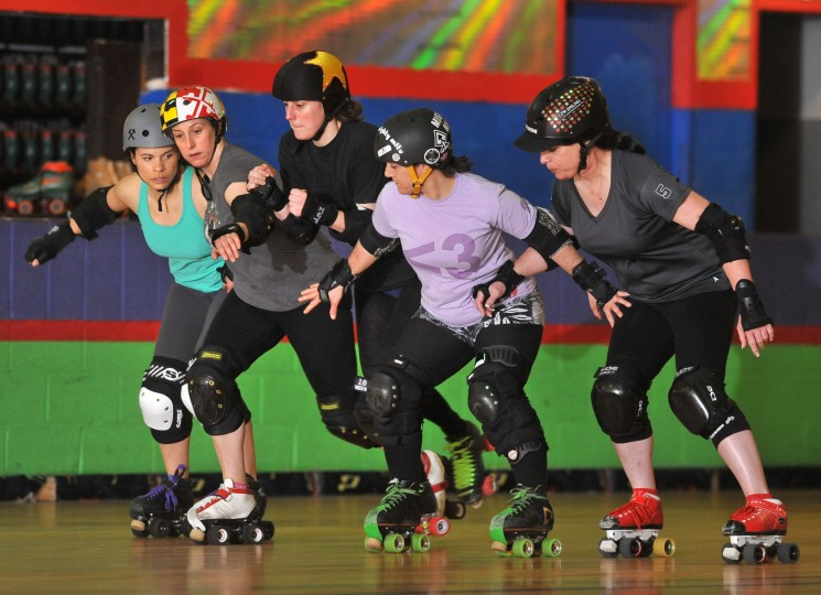 In the role of jammer, Jeanne Dark, third from left (wearing star cover on her helmet) tries to get through a line of four blockers, from left, Beta Blockher, Lady Quebeaum, Mighty Mite, and DB Velocette, at a Bootcamp training session for the Charm City Roller Girls held at Skateland North Point. (Amy Davis / Baltimore Sun)