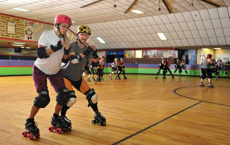 Kate Meehan, left, and Holly Gohardly practice seal blocking with a partner, creating a wall to prevent opposing skaters from passing, during a Bootcamp training session for the Charm City Roller Girls held at Skateland North Point. (Amy Davis / Baltimore Sun)