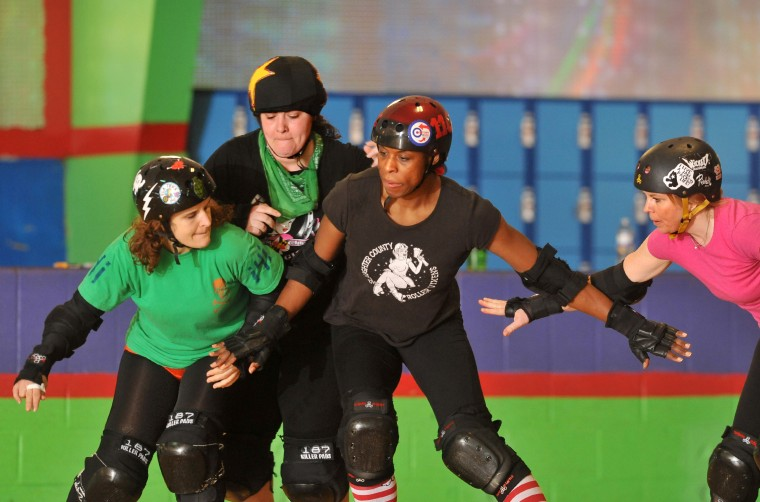 In front from left, Ela Trick, Uvetta Work, and Red Pepper try to hold back Guantanamurder, (wearing the jammer's star cover on her helmet), from passing them, at a Bootcamp training session for the Charm City Roller Girls held at Skateland North Point. (Amy Davis / Baltimore Sun)