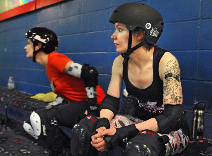 Sadie Stingray, left, and McJagged, right, watch the practice during their brief moments on the bench, at a Bootcamp training session for the Charm City Roller Girls held at Skateland North Point. (Amy Davis / Baltimore Sun)