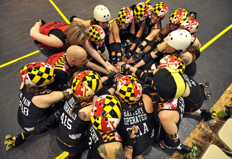 Charm City Roller Girls' All Stars touch hands and cheer to end their huddle before facing Philly's Roller Girls, the Liberty Belles. Baltimore lost to Philly in the second game by 231 to 129. (Amy Davis / Baltimore Sun)
