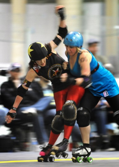 Susy Pow, jammer for the Charm City Roller Girls' All Stars, left, gets knocked down by Damage Dahl of the Philly Roller Girls' Liberty Belles. (Amy Davis / Baltimore Sun)