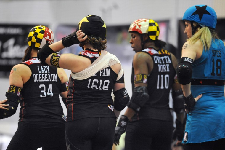 "The two opposing jammers, who wear star covers on their helmets, wait with their teams for the start of the next two minute ""jam."" From left, Baltimore's All Stars' Lady Quebeaum, I.M. Pain, and Uvetta Work are in position in front of VanEssa ""V-Diva"" Sites of the Philly Liberty Belles, far right. (Amy Davis / Baltimore Sun)"