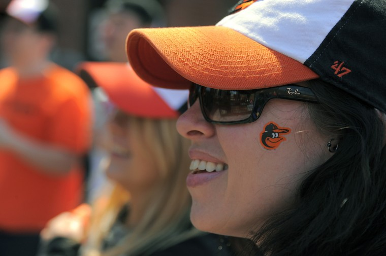 Fans Sarah Kidwell (left) and Colleen Lease gather to watch the band The Qi Lo outside the stadium for the Baltimore Orioles' home opener at Oriole Park at Camden Yards. (Karl Merton Ferron/Baltimore Sun)