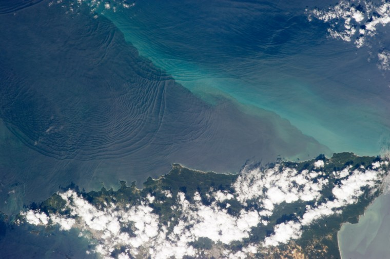 """This photograph, taken from the International Space Station (ISS), shows the north coast of Trinidad and a series of subtle, interacting arcs in the southeastern Caribbean Sea. These are known as """"internal waves,"""" the surface manifestation of slow waves that move tens of meters beneath the sea surface. Internal waves produce enough of an effect on the sea surface to be seen from space, but only where they are enhanced due to reflection of sunlight, or sun glint, back towards the International Space Station. NASA image"""