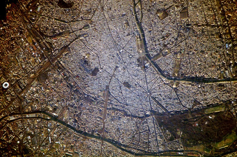 """A crisp, clear winter day over France provided the International Space Station a detailed view of the city of Paris. This image, rotated and cropped from the original, shows the recognizable street pattern of the city—and some of the world's most notable landmarks—along the Seine River. One of the main avenues radiating like spokes from the Arc de Triomphe (image upper left) is the Avenue des Champs-Élysées running southeast to the Garden of Tuileries (Jardin des Tuileries). The garden—recognizable by its light green color relative to the surrounding built materials—was originally commissioned by Catherine de Medici in 1559, and is now bounded by the Place de la Concorde to the northeast and the Louvre museum along the Seine River at the southeast end. Other, similarly colored parks and greenspaces are visible throughout the image. Farther south on the Seine is the Íle de la Cité, location of the famous Notre Dame cathedral. Perhaps most prominent is the characteristic """"A"""" profile of the Eiffel Tower west of the Jardin des Tuileries, highlighted by morning sunlight. NASA image"""