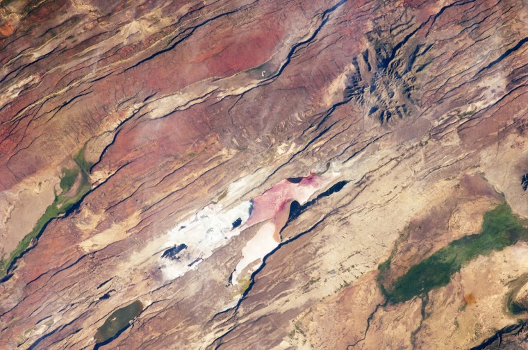 The East African Rift is one of the great tectonic features of Africa, caused by fracturing of the Earth's crust. This astronaut photograph of the Eastern Branch of the Rift (near Kenya's southern border) highlights the classical geologic structures associated with a tectonic rift valley. On one side of the rift lies the Nubian (or African) tectonic plate, which includes the older continental crust of Africa. The Somalian plate—which is moving away in the other direction—lies to the other side and includes the Horn of Africa. (Note that the image is oriented so that north is to the lower left.) Together with the associated Ethiopian Rift, the tectonic boundary stretches from the southern Red Sea to central Mozambique. NASA image