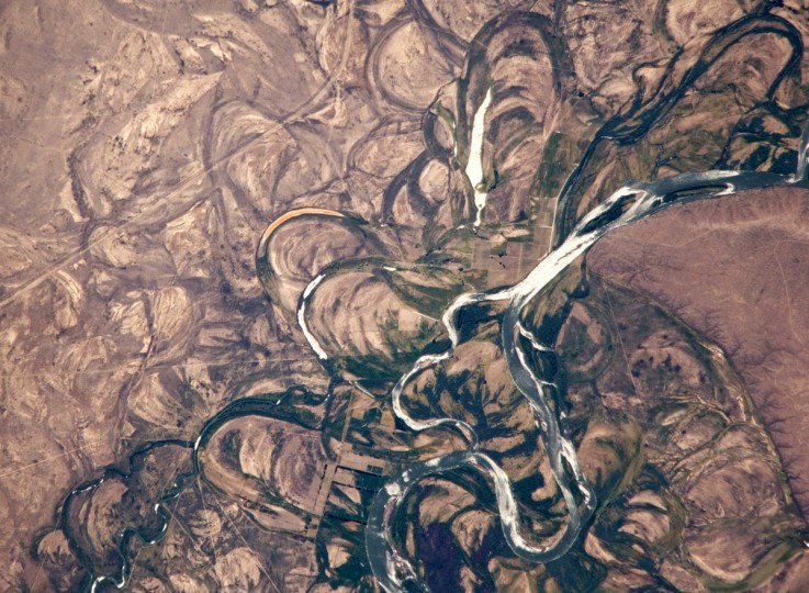 The Rio Negro is recognizable by astronaut crews from orbit as one of the most meandering rivers in South America. In this astronaut photograph, the entire floodplain (mostly 10 kilometers wide) is covered with curved relics of channels known as meander scars. Meander scars show the past positions of river bends. The Rio Negro is a dramatic example of how mobile a river can be; these meanders were produced as the river snaked across the plain in the very recent geological past, probably during the last few hundred years. The main channel of the river, flowing south at this point - sixty kilometers south of the city of Choele Choel (not shown) - appears in partial sun glint at image right. Sun glint occurs when light is reflected off a water surface directly back towards the viewer, like a mirror, imparting a silvery sheen to those areas. When meander scars contain water they are known as oxbow lakes, some of which are also highlighted by sun glint in the image. NASA image