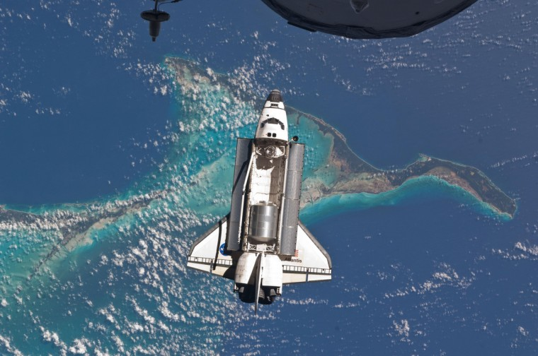In this astronaut photograph, the Space Shuttle Atlantis approaches the International Space Station for docking for the last time on July 10, 2011. Part of a Russian Progress spacecraft, also docked to the station, pokes into the upper foreground. Beneath them all lie the teal-colored shallows around the Bahamas. NASA image