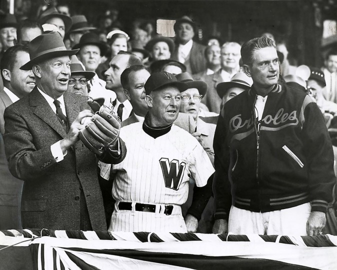 1957: President Eisenhower throws out the first pitch at Opening Day as Managers Chuck Dressen (Senators) and Paul Richards (Orioles) watch. The pitch kicks off the Baltimore Orioles vs. Washington Senators game. (Robert F. Kniesche/Baltimore Sun)