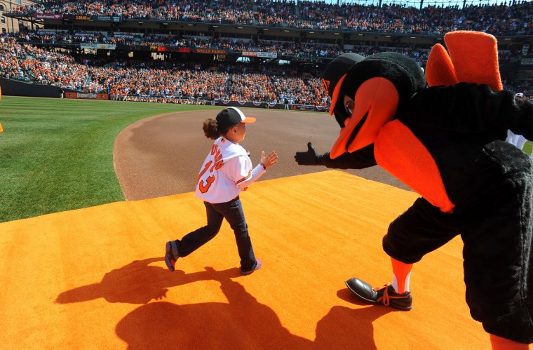 A young fan is greeted by the Oriole Bird as she is introduced as the 10th man. (Kenneth K. Lam/Baltimore Sun)