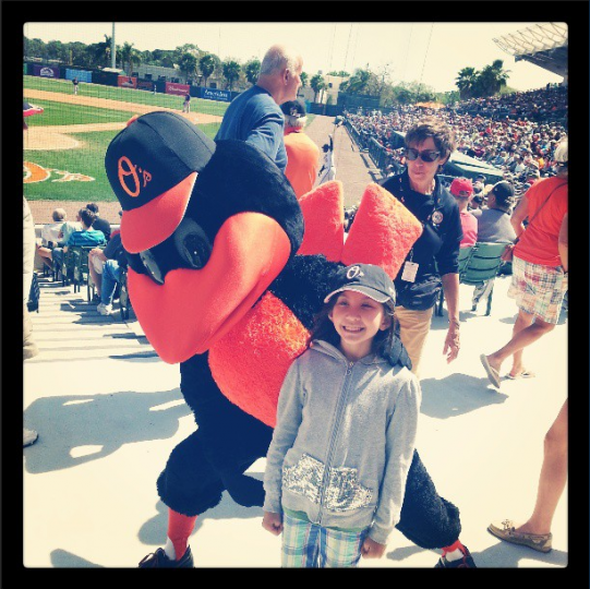 A young girls poses with the Orioles mascot in the lower deck stands