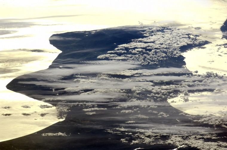 "This astronaut photograph shows the Calabria region of southern Italy - the toe of Italy's ""boot"" - outlined by the Ionian and Tyrrhenian Seas to the southeast and northwest respectively. The water surfaces present a mirror-like appearance due to sunglint. This phenomenon is caused by sunlight reflecting off the water surface directly back towards the astronaut observer on board the International Space Station (ISS). The ISS was located over northwestern Romania, approximately 1,040 kilometers to the northeast of Calabria, when this image was taken. The Calabrian Peninsula appears shortened and distorted due to the extreme sideways viewing angle from the ISS. Such a perspective is termed oblique, as opposed to a nadir view, in which the astronaut is looking directly downwards towards the Earth's surface from the ISS. This highly oblique view also highlights two distinct cloud patterns over the Calabrian interior."
