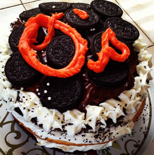 "Oreo cookie cake with orange ""O's"" lettering in icing on top"