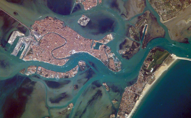 A space-based perspective of the city of Venice quickly reveals different development and land uses in the region; the major islands in the lagoon surrounding Venice - Laguna Veneta - look different from one another. The island of Venice itself, a dense urban landscape, appears almost uniformly covered with red-tiled roofs. By contrast, port facilities and the train station at the west end of the island appear in shades of gray. Though Venice's population is fewer than 70,000 residents and declining, as many as 12 million people visit the city every year. Many arrive from the mainland via the bridge at the train station. Many also arrive by boats; boat wakes can be seen as white flashes in many parts of the image. A prominent visual feature of the Venice metropolitan area is the S-bend of the Grand Canal. The famous Rialto Bridge is big enough to appear as a white break in the canal in this astronaut photograph. NASA image