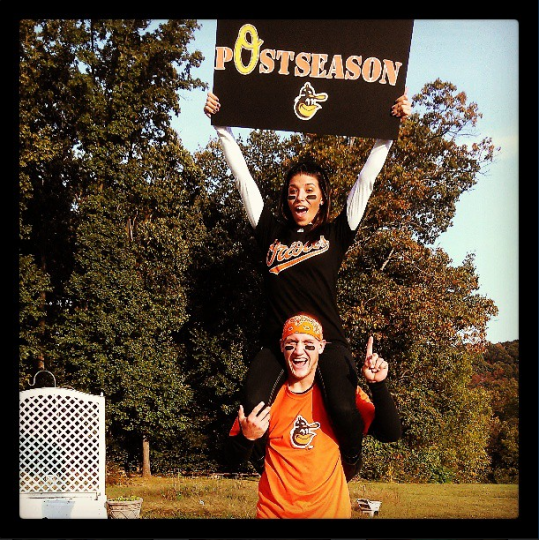 "A young man with his girlfriend on his shoulders, who's holding an orange and black ""Postseason"" sign, both decked out in Orioles gear, celebrate the team's entry into the playoffs."