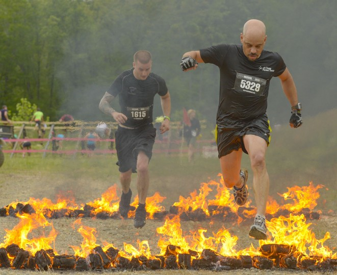 Jeff Mitchell (right) and Dustin Callender near the home stretch as they clear the fire obstacle at a Warrior Dash in Mechanicsville, Md. May 18, 2013. (Doug Kapustin/Baltimore Sun)