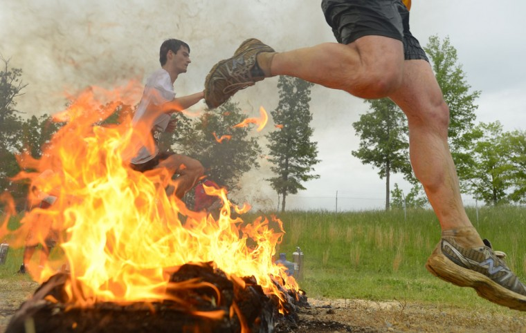 Nathan George (left) and Fred Forney clear the fire obstacle as they head into the home stretch of a Warrior Dash in Mechanicsville, Md. May 18, 2013. (Doug Kapustin/Baltimore Sun)