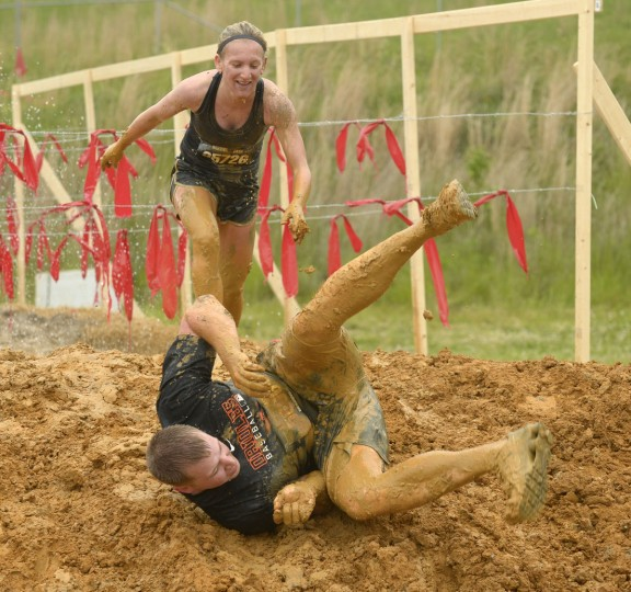 Chris Neuman takes a fall while running partner, Kim Howell and he clear the mud pit and approach the finish line at a Warrior Dash in Mechanicsville, Md. May 18, 2013. (Doug Kapustin/Baltimore Sun)
