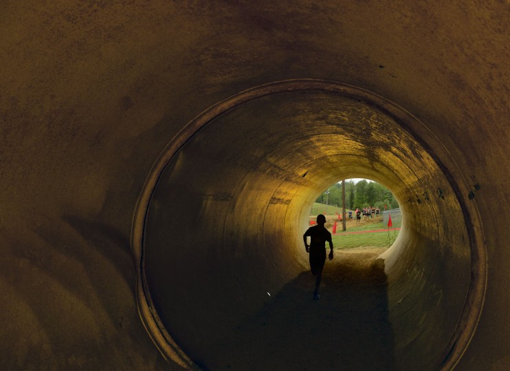 Athletes run through a tunnel to their next obstacle midway through the course at a Warrior Dash in Mechanicsville, Md. May 18, 2013. (Doug Kapustin/Baltimore Sun)