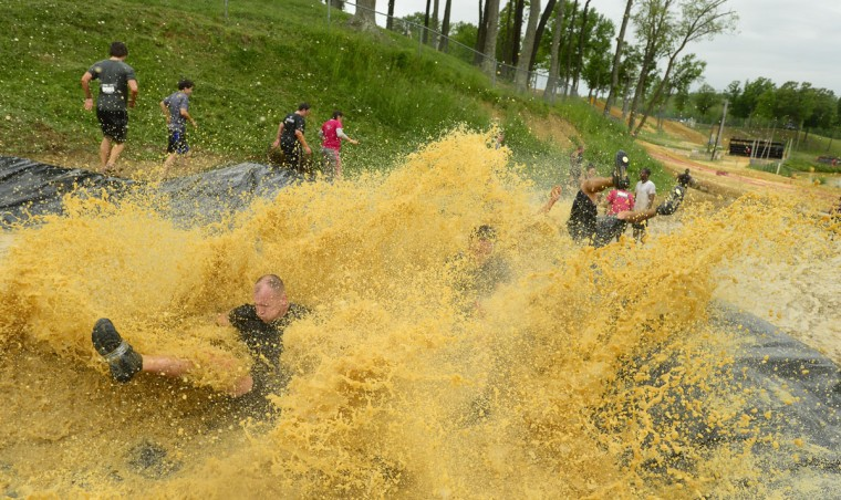 "Mark Yingling hits the bottom of the ""slip and slide"" obstacle as other athletes escape the watery pit and move on to their next challenge at a Warrior Dash in Mechanicsville, Md. May 18, 2013. (Doug Kapustin/Baltimore Sun)"