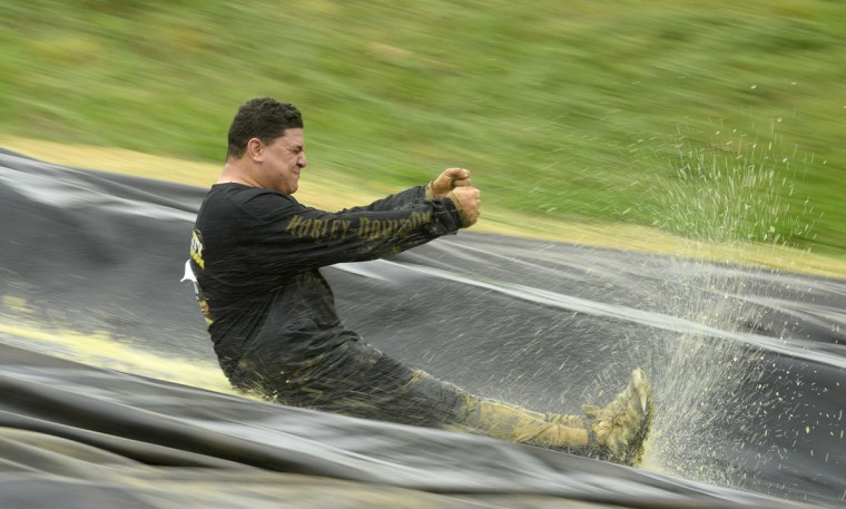 "Dustin Buter enjoys his quick trip down the ""slip and slide"" obstacle during a Warrior Dash in Mechanicsville, Md. May 18, 2013. (Doug Kapustin/Baltimore Sun)"