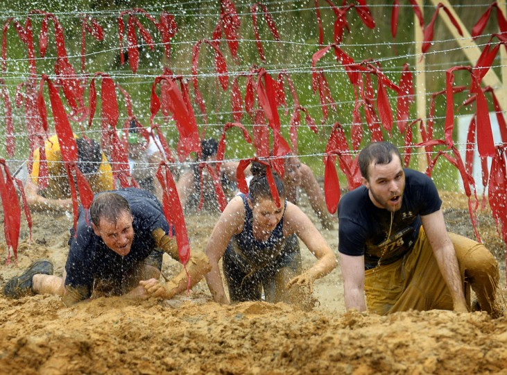 Steven Anderson (right) leads a group under the wire and through the mud as they near the finish line. at a Warrior Dash in Mechanicsville, Md. May 18, 2013. (Doug Kapustin/Baltimore Sun)