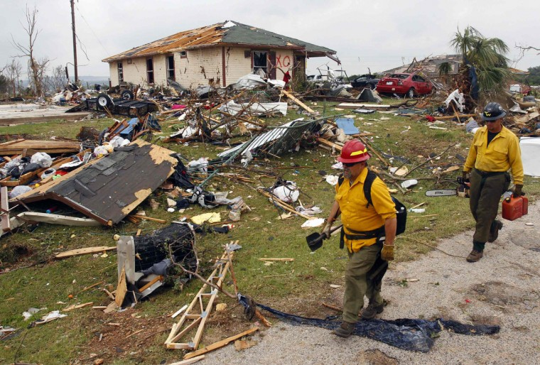 Rescue workers walk past debris May 16 after tornados swept through the town of Granbury, Texas late May 15, 2013. At least six people were killed and about 100 injured on Wednesday as three tornadoes ripped through a stretch of Texas near the Dallas-Fort Worth area, destroying a number of homes, authorities said. (Richard Rodriguez/Reuters)