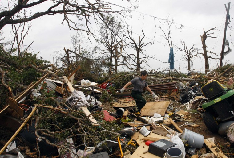 A firefighter walks through debris May 16, 2013, after tornados swept through the town of Granbury, Texas late May 15. At least six people were killed and about 100 injured on Wednesday as three tornadoes ripped through a stretch of Texas near the Dallas-Fort Worth area, destroying a number of homes, authorities said. (Richard Rodriguez/Reuters)