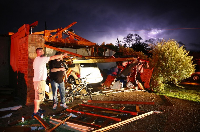 Derrek Grisham, left, points out neighborhood damage to storm chaser Travis Schafer on Wednesday May 15, 2013, in Cleburne, Texas, after overnight storms sparked tornadoes and caused damage to the area. (Tom Tox/Dallas Morning News/MCT)