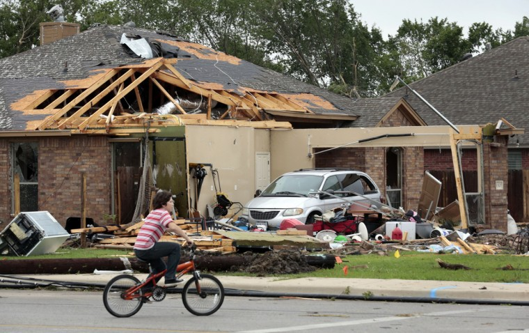 A child rides by damaged home on Thursday, May 16, 2013, in Cleburne, Texas, after overnight storms sparked tornadoes and caused damage to the area. (Michael Ainsworth/Dallas Morning News/MCT)