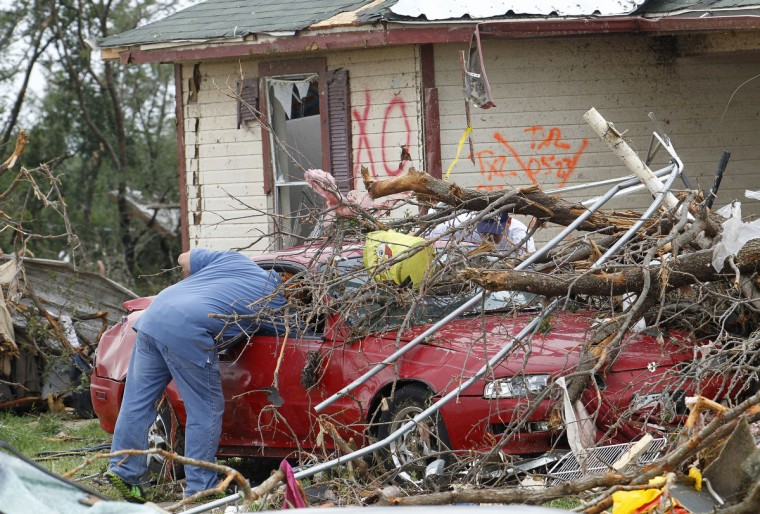 Emergency personnel search around a crushed car on Thursday, May 16, 2013, in Granbury, Texas, after overnight storms sparked tornadoes and caused damage to the area. (Paul Moseley/Fort Worth Star-Telegram/MCT)