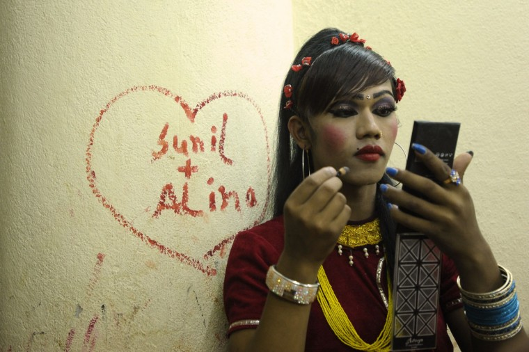 A Nepalese transgendered performer puts on make up backstage for an event on the International Day Against Homophobia and Trans-phobia in Kathmandu. Nepal, home to Asia's leading gay and transgender rights movement, legally recognizes a third gender category on documents for transgender people. (Prakash Mathema/AFP/Getty Images)